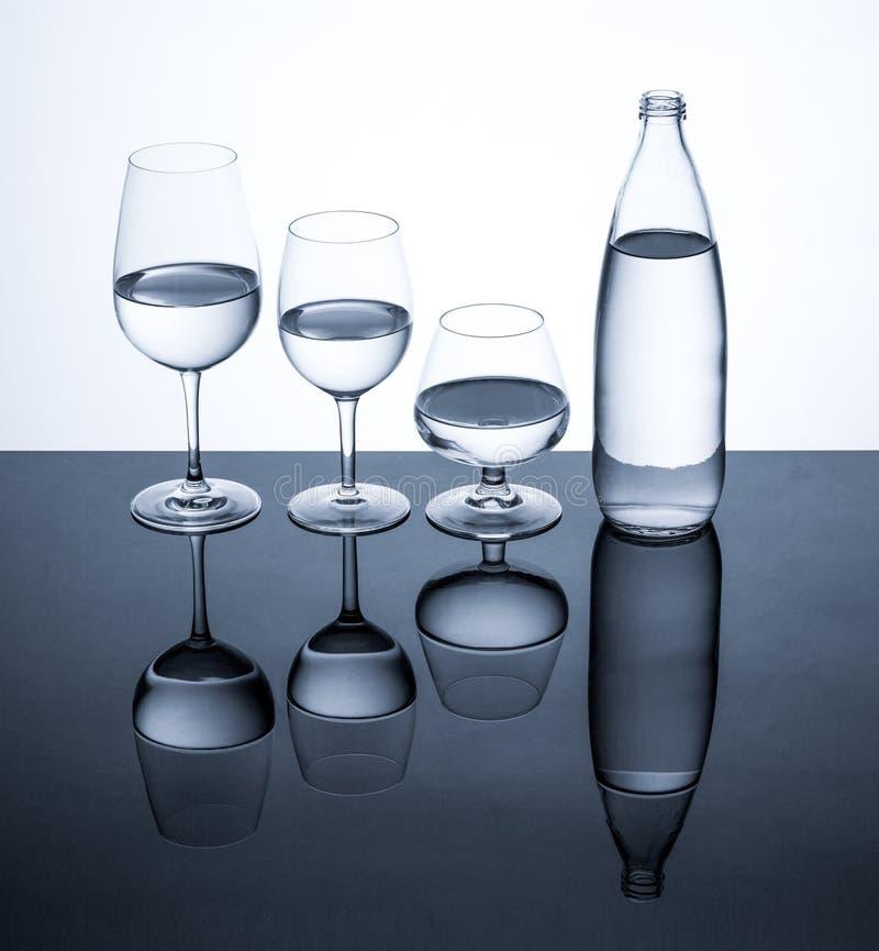 La verrerie et la bouteille ont rempli avec de l'eau sur le fond blanc photos stock