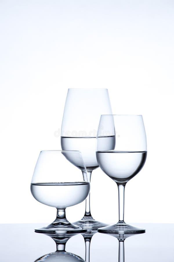 La verrerie et la bouteille ont rempli avec de l'eau sur le fond blanc images libres de droits
