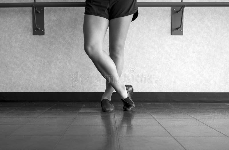 La versión blanco y negro de los zapatos del jazz en un bailarín del jazz con el pie cruzó encima fotografía de archivo
