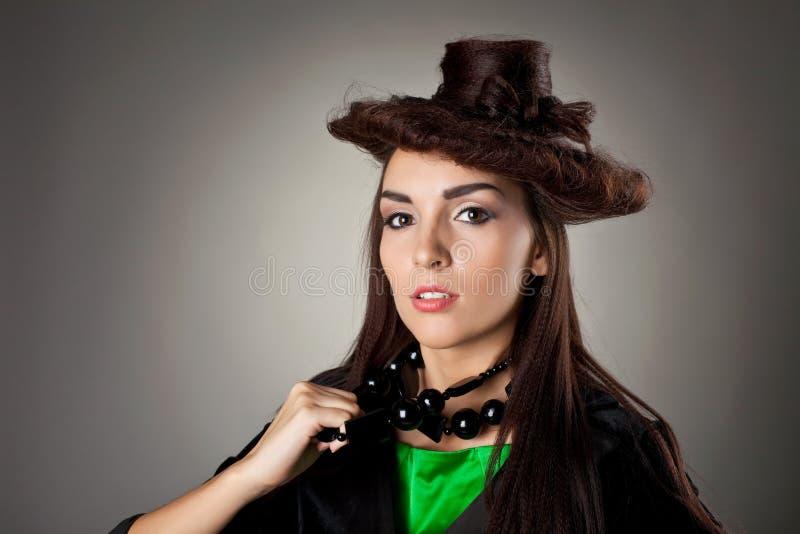 La verticale de femme dans le type de cheveu aiment le chapeau photos libres de droits