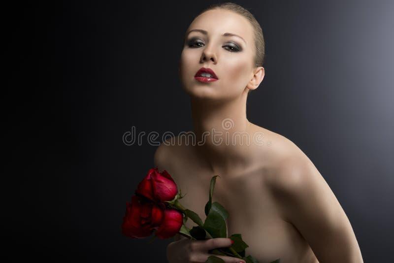 La verticale discrète de Gilr avec des roses s'approchent du coffre image stock