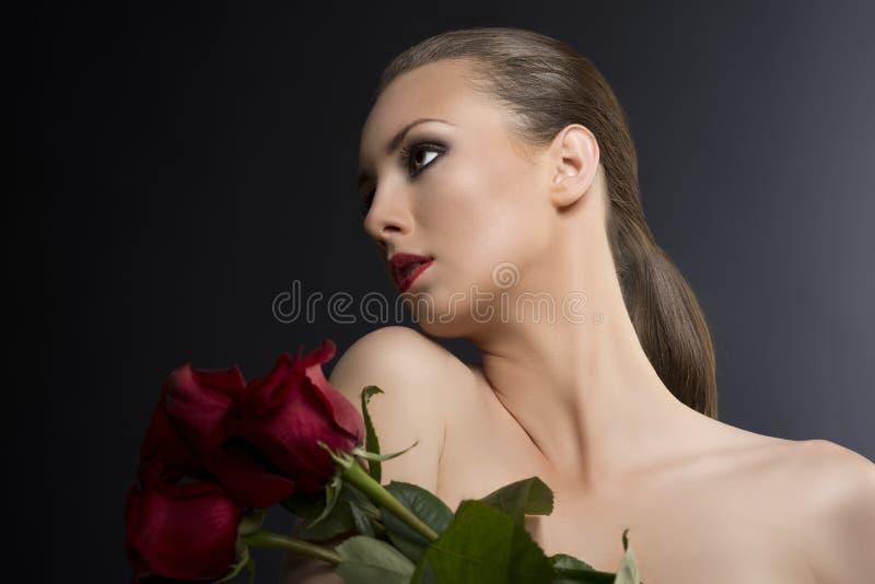 La verticale discrète de la fille avec des roses photo stock