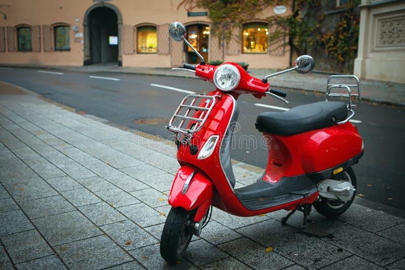 La vespa rossa iconica, motociclo italiano antiquato, è parcheggiata sul marciapiede della via nel centro di Salisburgo fotografia stock