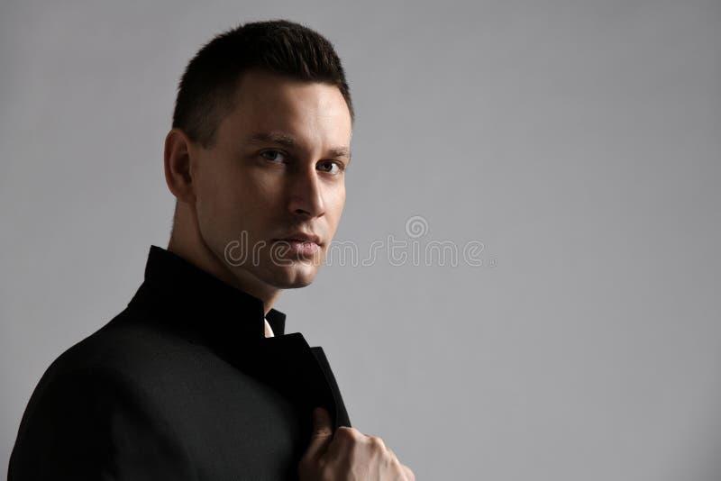 La veste élégante pleine d'assurance d'homme moderne qu'il tient sur les laples se tient en longueur à nous Fond rougeoyant de ce image stock