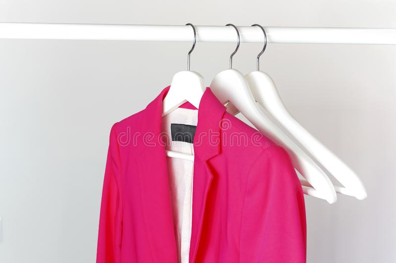 La veste des femmes intelligentes de rose sur le cintre de manteau en bois blanc sur la tige contre l'espace étendu plat de copie image libre de droits