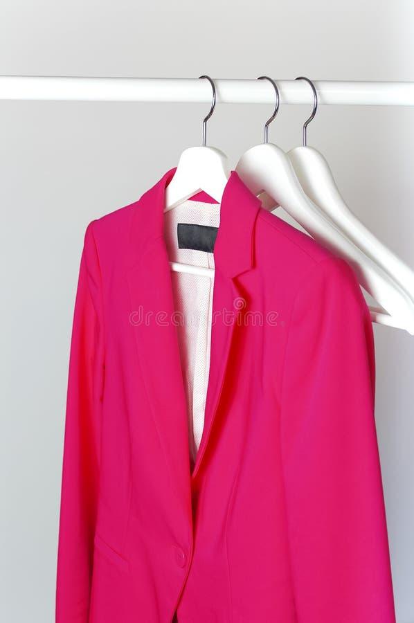 La veste des femmes intelligentes de rose sur le cintre de manteau en bois blanc sur la tige contre l'espace étendu plat de copie photos stock