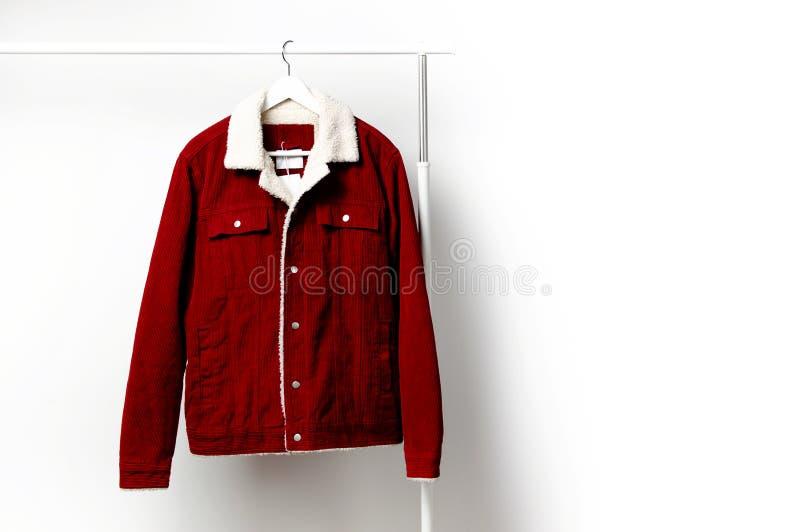 La veste des hommes rouges de velours côtelé sur le cintre de manteau blanc sur la tige contre l'espace étendu plat de copie de m images stock