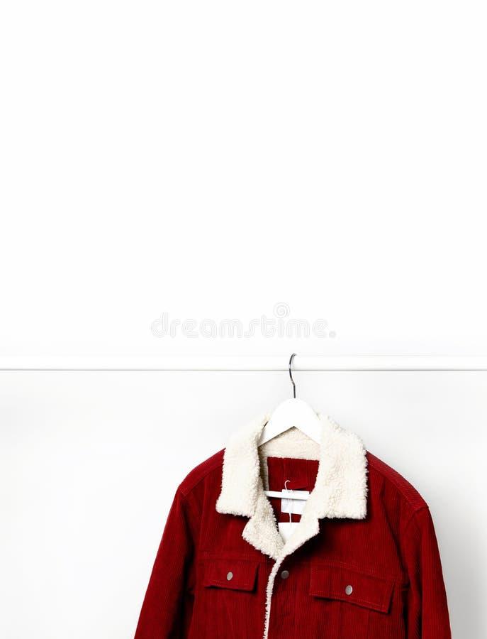 La veste des hommes rouges de velours côtelé sur le cintre de manteau blanc sur la tige contre l'espace étendu plat de copie de m photo libre de droits
