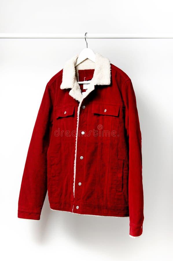 La veste des hommes rouges de velours côtelé sur le cintre de manteau blanc sur la tige contre l'espace étendu plat de copie de m photos libres de droits
