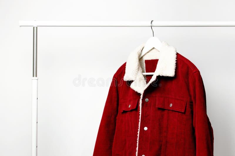 La veste des hommes rouges de velours côtelé sur le cintre de manteau blanc sur la tige contre l'espace étendu plat de copie de m photos stock