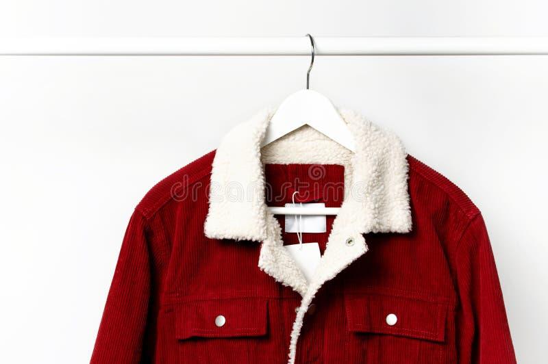 La veste des hommes rouges de velours côtelé sur le cintre de manteau blanc sur la tige contre l'espace étendu plat de copie de m photographie stock