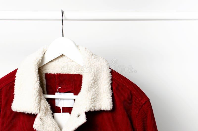 La veste des hommes rouges de velours côtelé sur le cintre de manteau blanc sur la tige contre l'espace étendu plat de copie de m photo stock