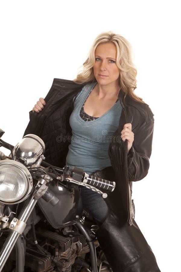 La veste en cuir ouverte de femme se reposent sur la moto images stock
