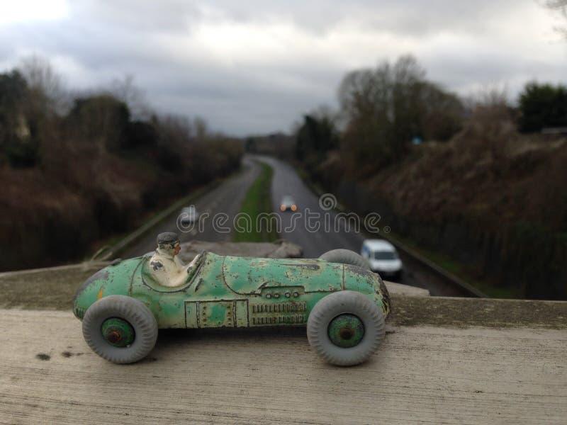 La vettura da corsa del giocattolo d'annata, fine indossata verde della pittura su, visto da sopra una strada principale ha offus fotografia stock