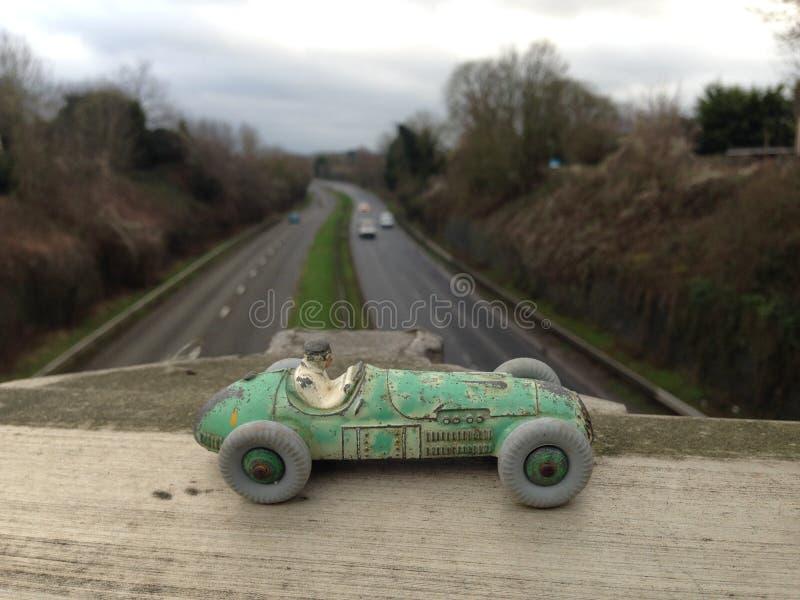 La vettura da corsa del giocattolo d'annata, fine indossata verde della pittura su, visto da sopra una strada principale ha offus immagine stock
