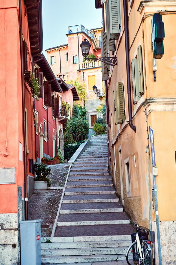 La via antica stretta fiorisce il centro variopinto Verona dell'Italia della facciata di punti della pietra del marciapiede immagine stock