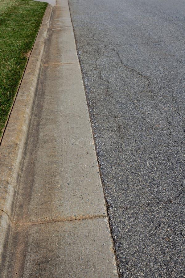 La via residenziale con il bordo formato ed ha orlato piacevolmente l'erba fotografia stock libera da diritti