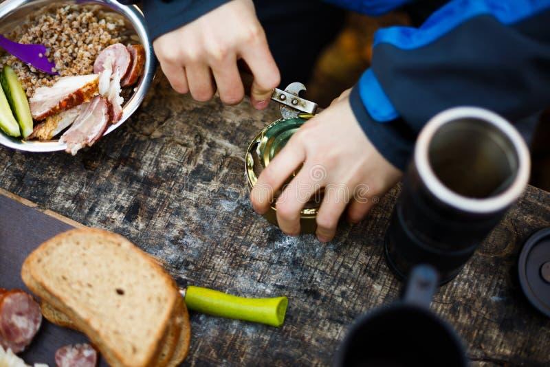 La viandante apre le latte sulla tavola di legno durante la prima colazione al campo della foresta La gente che si accampa al par immagine stock