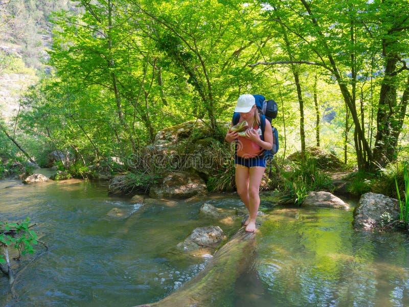 La viandante attraversa un fiume fotografia stock