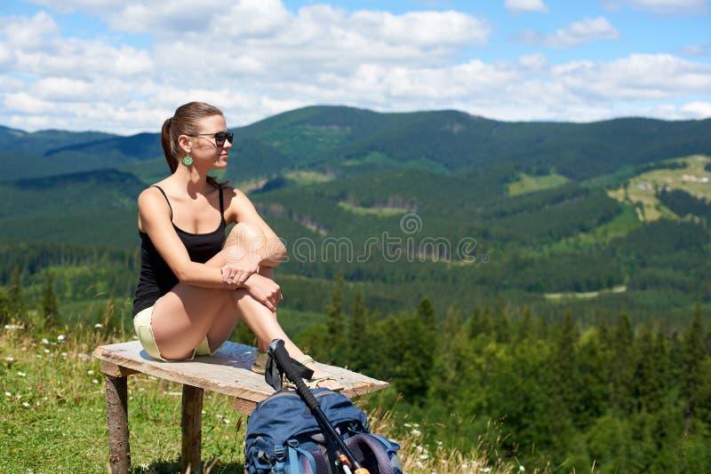 La viandante della donna che fa un'escursione sulla collina erbosa, zaino d'uso, facendo uso del trekking attacca nelle montagne fotografia stock
