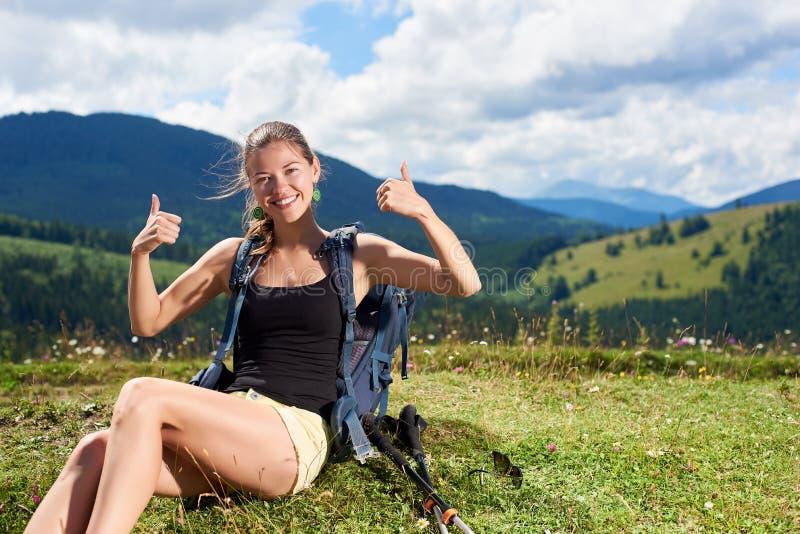 La viandante della donna che fa un'escursione sulla collina erbosa, zaino d'uso, facendo uso del trekking attacca nelle montagne immagine stock