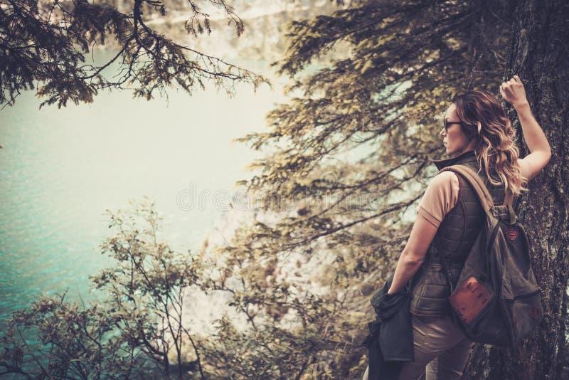 La viandante della donna con lo zaino che gode del lago stupefacente della montagna abbellisce fotografia stock libera da diritti