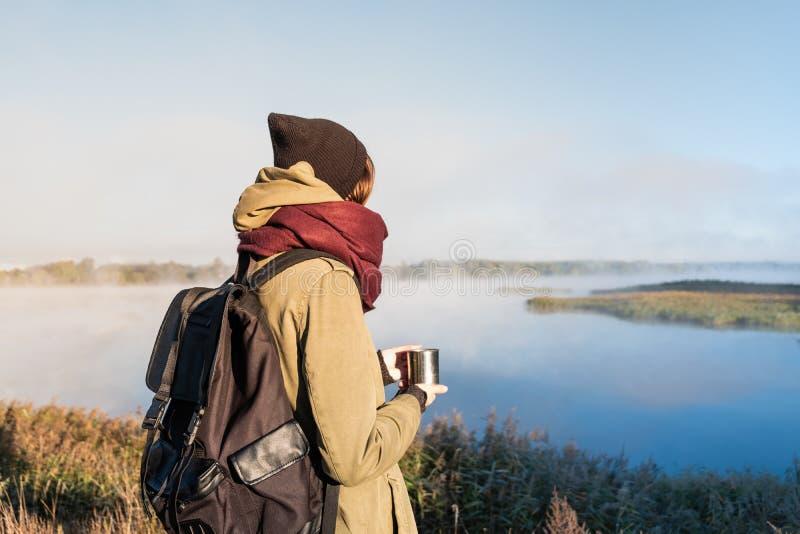 La viandante della donna gode di bello paesaggio della natura con una tazza del Dott. caldo immagine stock libera da diritti