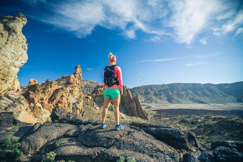 La viandante della donna ha raggiunto la cima della montagna, avventura di viaggiatore con zaino e sacco a pelo immagine stock libera da diritti