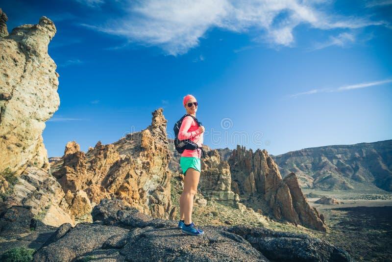 La viandante della donna ha raggiunto la cima della montagna, avventura di viaggiatore con zaino e sacco a pelo fotografie stock