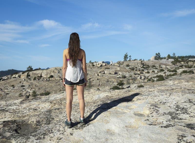 La viandante della giovane donna esamina il terreno roccioso immagine stock libera da diritti