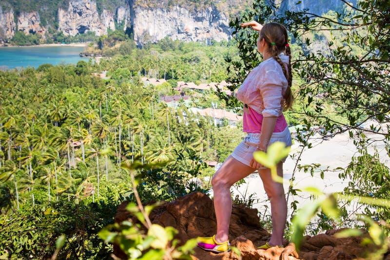 La viandante della giovane signora con le trecce dei capelli esamina la distanza e vista godere della spiaggia tropicale dalla ci fotografia stock libera da diritti