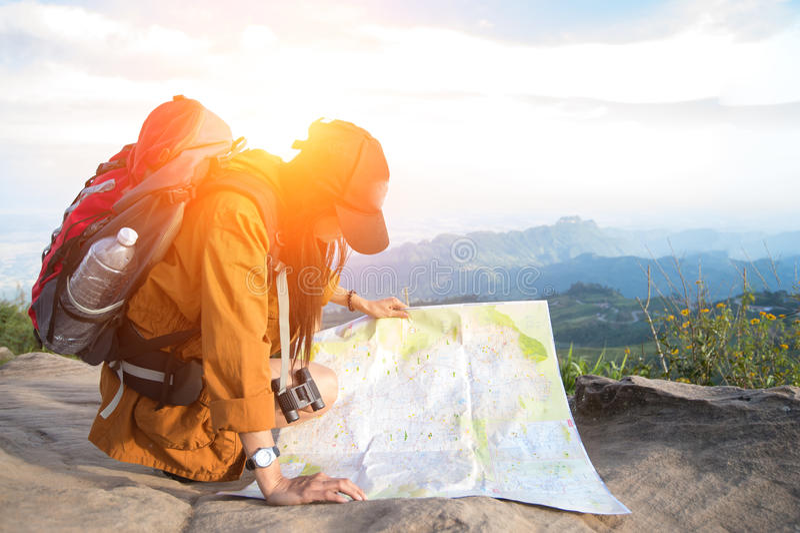 La viandante delle donne con lo zaino controlla la mappa fotografia stock libera da diritti