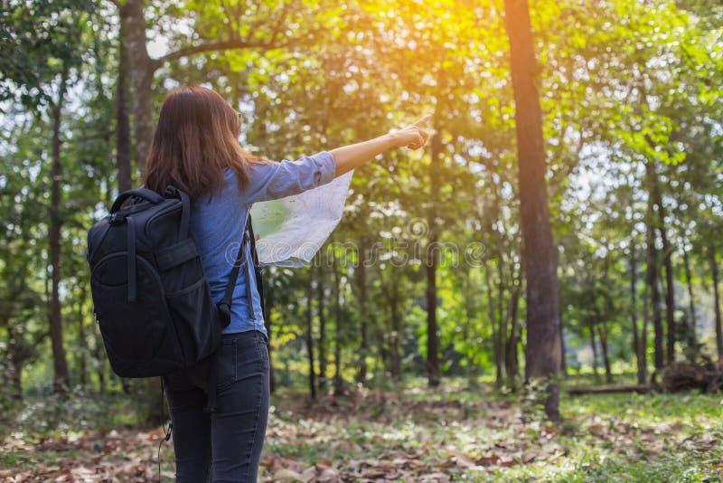 La viandante delle donne con lo zaino controlla la mappa per trovare le direzioni nell'area di regione selvaggia fotografia stock libera da diritti