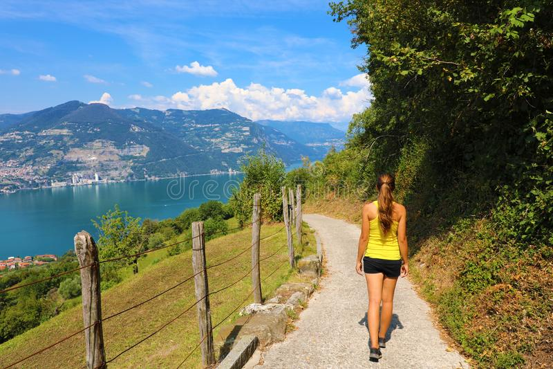 La viandante femminile va giù e discesa la via con paesaggio spettacolare del lago Iseo da Monte Isola, Lombardia, Italia fotografie stock
