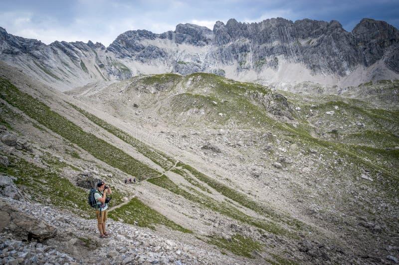 La viandante prende le immagini su un passo di montagna delle alpi di Allgau fotografie stock libere da diritti