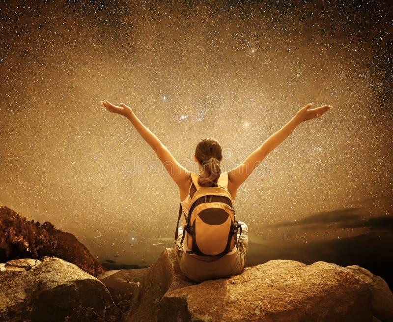 La viandante si siede sopra una montagna e godere della vista del cielo notturno con fotografie stock libere da diritti