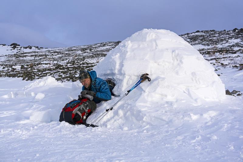La viandante si versa un tè da un termos, sedentesi in un iglù nevoso della capanna immagini stock