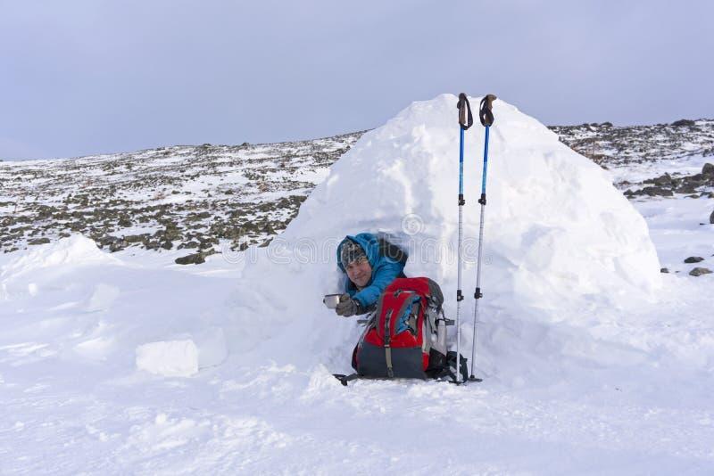 La viandante sorridente offre una tazza di tè mentre si siede in un iglù nevoso della capanna nell'inverno immagini stock libere da diritti