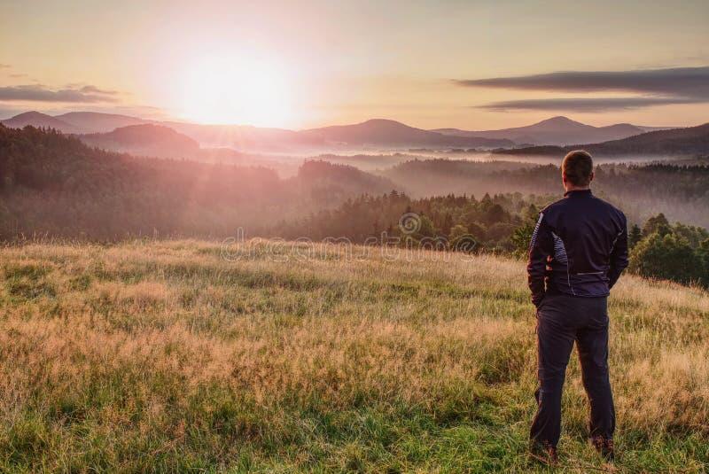 La viandante sta e gode della vista della valle dalla collina immagini stock