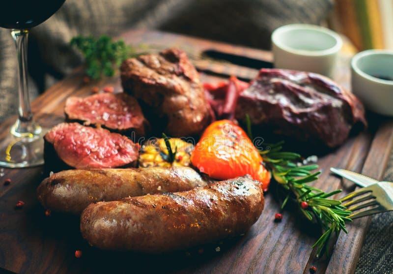 La viande de mélange grillée sur le conseil avec le vin rouge image stock