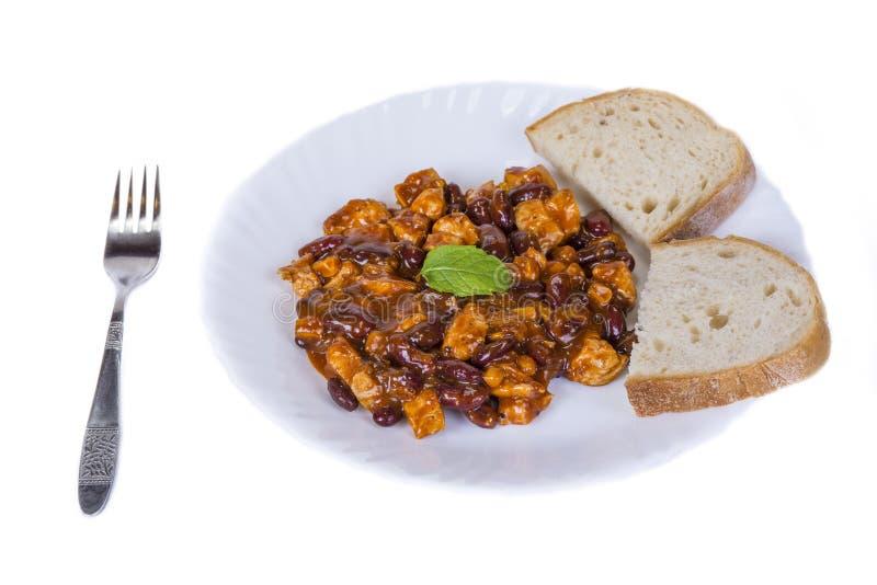La viande de poulet avec des haricots sauce avec du pain du plat sur le blanc images stock