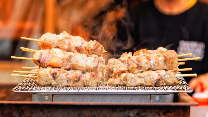 La viande de thon avec le bâton a grillé avec de la fumée, nourriture japonaise de rue image stock