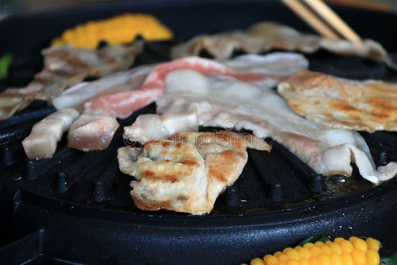 La viande, le lard et le porc rayé ont grillé sur le gril électrique noir avec l'ébullition de maïs images libres de droits