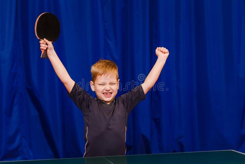 La victoire dans la manifestation sportive, l'enfant est heureuse de gagner dans le ping-pong photo stock