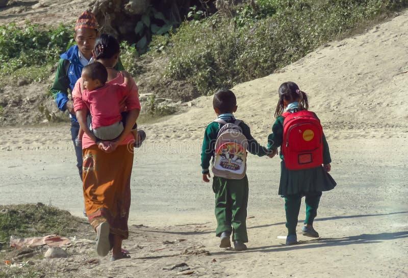 La vida cotidiana en Nepal, niños en uniforme camina de común acuerdo a la escuela, madre lleva a un pequeño niño en ella detrás fotos de archivo libres de regalías