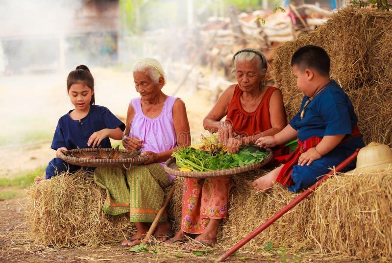 La vida de cada día rural tailandesa asiática tradicional, nietos en trajes culturales ayuda a sus mayores que preparan los ingre fotos de archivo libres de regalías