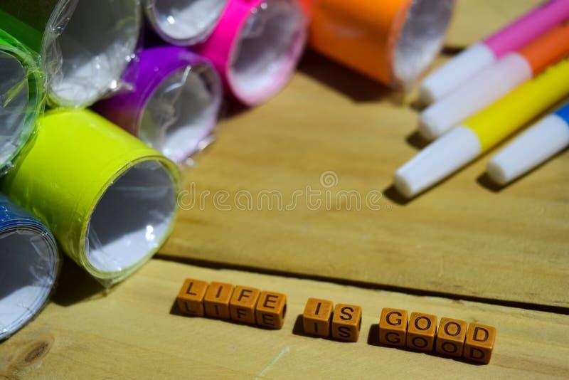 La vida es buena en los cubos de madera con el papel y la pluma coloridos, inspiración del concepto en fondo de madera imagen de archivo