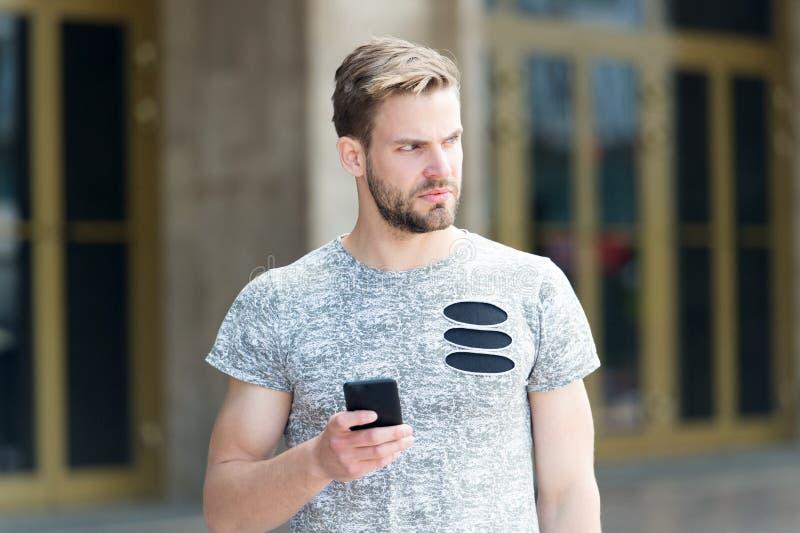 La vida moderna es imposible sin la comunicación celular Individuo moderno con smartphone en al aire libre urbano Hombre hermoso foto de archivo libre de regalías