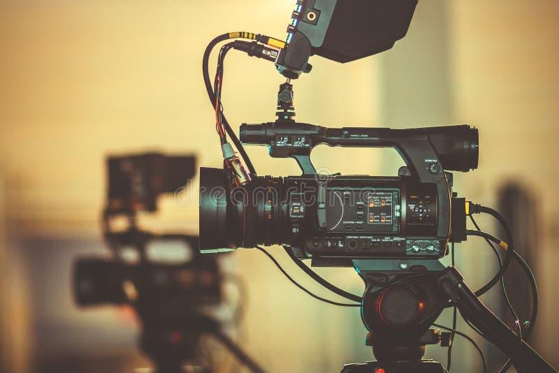 La videocamera professionale sta su un treppiede, il processo di ripresa del film dagli angoli differenti immagini stock