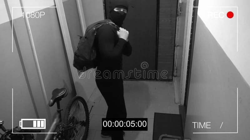 La videosorveglianza ha preso il ladro in una maschera che cola con una borsa del bottino, mostra alla macchina fotografica il di fotografia stock